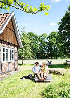 Paar mit Buch auf Holzliege - p606m924825 von Iris Friedrich