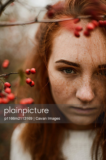 Close-up portrait of teenage girl with red head - p1166m2113169 by Cavan Images