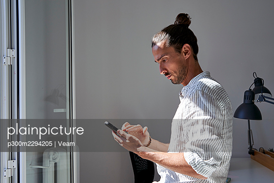 Male professional using mobile phone in front of window at office - p300m2294205 by Veam