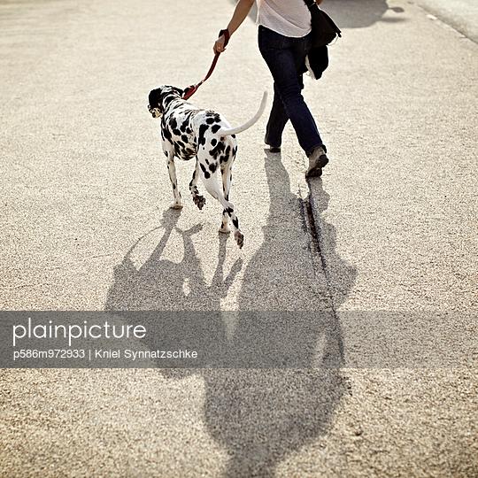 Junge Frau macht einen Spaziergang mit ihrem Dalmatiner - p586m972933 von Kniel Synnatzschke