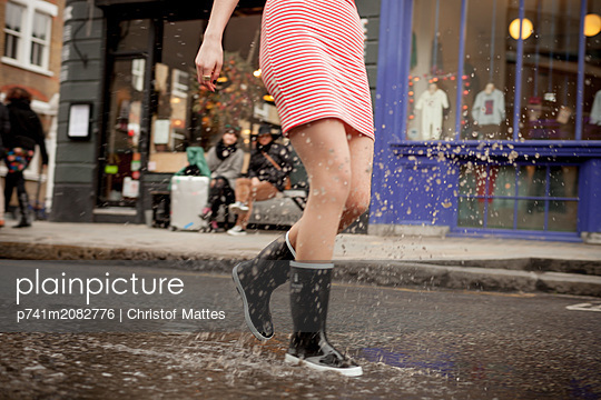 Junge Frau planscht in einer Pfütze - p741m2082776 von Christof Mattes