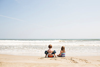 Rear view of siblings enjoying at beach against sky during sunny day - p1166m1403965 by Cavan Images