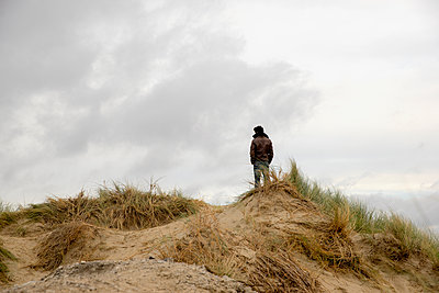Mann im Rückansicht auf einem Dünenhügel - p1212m1181973 von harry + lidy