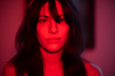Portrait of young woman in red light - p1321m2207403 by Gordon Spooner