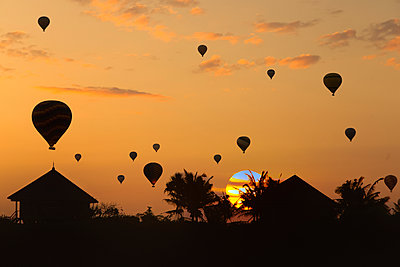 Indonesia, Bali, Silhouettes of hot air balloons flying over coastal huts at moody sunset - p300m2199177 by Konstantin Trubavin