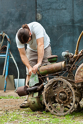 Man working on old rusty machine outdoors - p312m1552636 by Johner