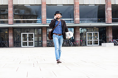 Male skateboarder strolling in city square making smartphone call, Freiburg, Baden-Wurttemberg, Germany - p429m2091589 by Sigrid Gombert