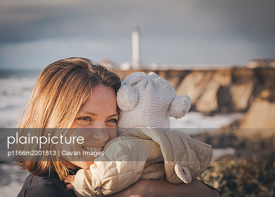 A woman is holding a baby near a lighthouse on the pacific coast - p1166m2201813 by Cavan Images