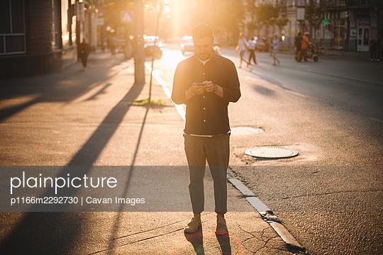 Man using smart phone standing on street in city against sunlight - p1166m2292730 by Cavan Images