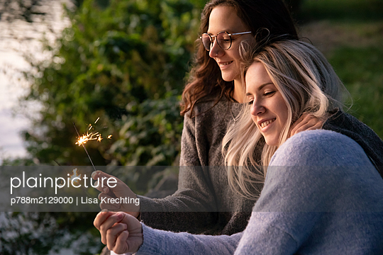 Two girlfriends with sparklers on the river bank - p788m2129000 by Lisa Krechting
