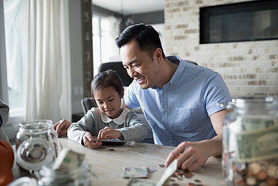 Father teaching daughter counting allowance money - p1192m1231391 by Hero Images