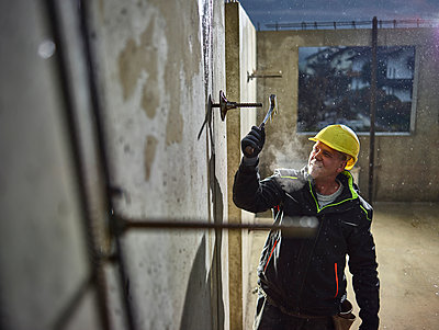 Construction worker fitting with hammer the iron rod - p300m2024084 by Christian Vorhofer