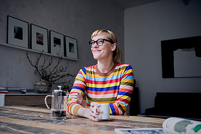 Portrait of smiling woman with cup of coffee in a loft - p300m2030235 by Rainer Berg