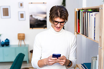Young man text messaging through smart phone while standing by bookshelf in living room - p300m2265901 by Giorgio Fochesato