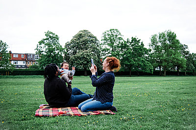 Woman photographing playful father with son at park - p300m2287206 by Angel Santana Garcia