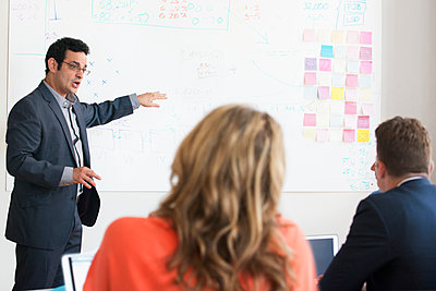 Businessman pointing to diagram on whiteboard in meeting - p555m1303471 by Jose Luis Pelaez Inc.