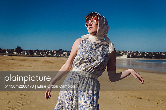 Woman in old fashioned dress and sunglasses on the beach - p1150m2260473 by Elise Ortiou Campion
