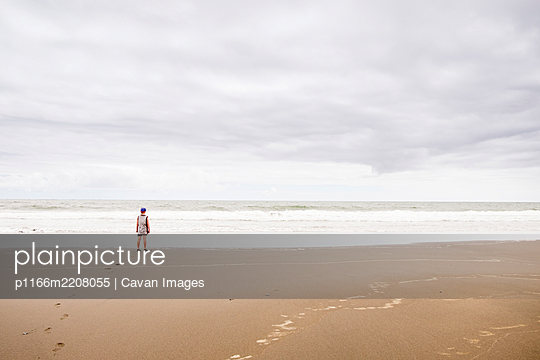 Young boy standing on the beach looking at the water - p1166m2208055 by Cavan Images