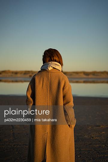 Frau im Mantel steht am Strand von St. Peter Ording - p432m2230459 von mia takahara