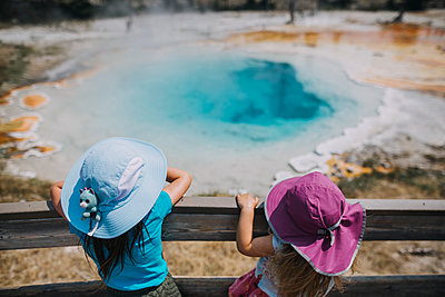 High angle view of sisters wearing hats while standing by wooden railing against hot spring at Yellowstone National Park - p1166m1561233 by Cavan Images