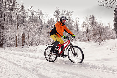 Man riding mountainbike on path in winter forest - p300m2083898 by Sebastian Dorn