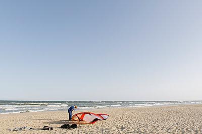 Male surfer preparing a kite at the beach - p300m2118705 by Hernandez and Sorokina