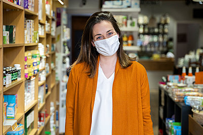 Young woman wearing protective face mask standing in grocery store - p300m2264467 by VITTA GALLERY