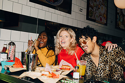Portrait of happy woman with friends eating burger during social gathering at cafe - p426m2194773 by Maskot
