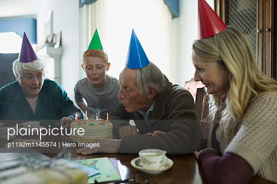 Senior man blowing birthday candles on cake at multi-generation family party