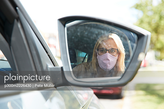 Reflection of woman wearing protective face mask sitting in car - p300m2226430 by Pete Muller