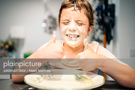 Smiling girl showing thumbs up while face smeared with flour and water - p300m2273602 by Albert Martínez