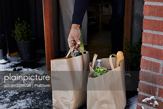 Hand holding paper bag with groceries - p312m2299726 by Plattform