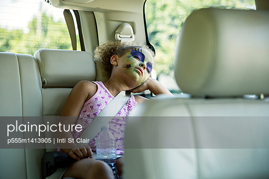 Mixed race girl in face paint sleeping in car back seat - p555m1413905 by Inti St Clair photography