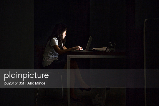 Woman in office working late - p62315135f by Alix Minde