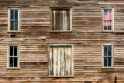Wooden house exterior with American flag in window,Oakesdale, Washington, USA - p1100m2084655 by Mint Images