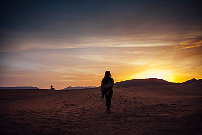 Rear view of woman standing on sand at desert against cloudy sky during sunset - p1166m1473779 by Cavan Images