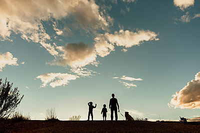 Silhouette father with sons and dog standing on field against cloudy sky during sunset - p1166m1544562 by Cavan Social