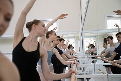 Ballet dancers practicing in a row at barre in dance studio - p1192m1403462 by Hero Images