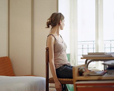 Junge Frau blickt zum Fenster - p1409m1465887 von margaret dearing
