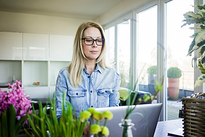 Portrait of blond businesswoman wearing glasses using laptop - p300m1587757 by Robijn Page