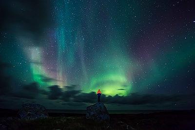 Norway, Lofoten Islands, Eggum, man standing on rock and watching northern lights - p300m2104630 von Valentin Weinhäupl
