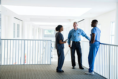 Doctor and nurses talking near staircase - p555m1532452 by FS Productions