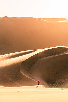 Walvis Bay, Namibia, Africa. Man walking on the sand dunes at sunset. - p651m2033384 by Marco Bottigelli