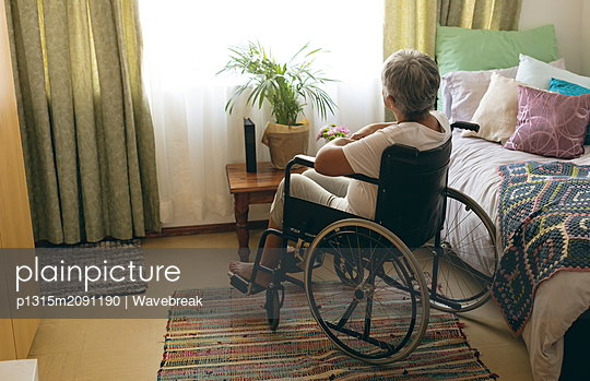 Disabled senior woman siting in wheelchair at retirement home - p1315m2091190 by Wavebreak