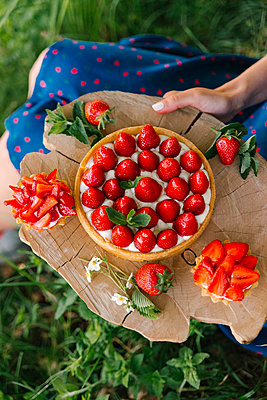 Midsection of woman holding strawberry cake on wooden board while sitting in yard - p1166m2065921 by Cavan Social