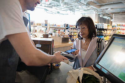 Worker helping active senior woman paying with smart phone contactless payment at grocery store checkout - p1192m1567209 by Hero Images