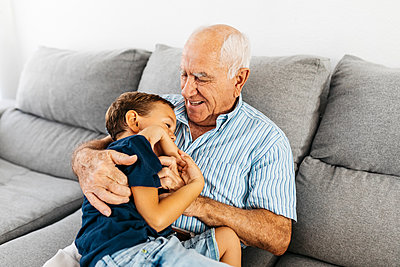 Grandson and grandfather laughing while tickling each other on the couch - p300m2029454 by Josep Rovirosa