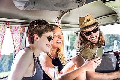 Happy friends inside van looking at smartphone - p300m2041842 by Jo Kirchherr