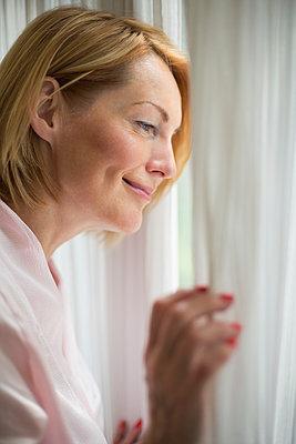 Smiling woman wearing bathrobe looking through window in bathroom - p301m1482447 by Vladimir Godnik