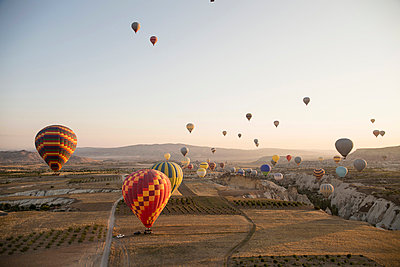 Large group of hot air balloons above field landscape, Cappadocia, Anatolia,Turkey - p429m1022631 by Guido Cavallini
